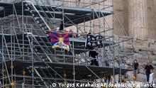 17.10.2021, Athen*** Demonstranten hissen eine tibetische Flagge und ein Banner von einem Baugerüst auf dem Akropolis-Hügel. Drei Personen versuchten, aus Protest gegen die bevorstehenden Olympischen Winterspiele in Peking ein Transparent von der Akropolis in Athen zu hängen, wurden aber verhaftet, bevor sie ihre Mission beenden konnten. Im antiken Olympia wird in einer feierlichen Zeremonie das olympische Feuer für die Winterspiele in Peking 2022 entzündet. Die Flamme wird anschließend nach Athen Reisen, wo das Olympischer Feuer am Dienstag, 19. Oktober, an das Pekinger Olympische Komitee übergeben wird. +++ dpa-Bildfunk +++