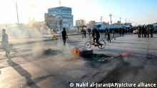 Supporters of hardline Iraqi Shiite factions block streets and burn tires after the Electoral Commission announced the results of the parliamentary elections in Basra, Iraq, Sunday, Oct. 17, 2021. Pro-Iran factions in Iraq suffered significant losses in parliament elections held on Oct. 10. (AP Photo/Nabil al-Jurani)