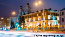 Minsk, Belarus. Night View Of Cathedral of Saint Virgin Mary And Building of French Embassy in Republic of Belarus. Traffic On Illuminated Pobedtiley Avenue Street In Minsk, Belarus.