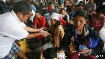 Villagers who live on the slope of Mount Sinabung receive food at a temporary shelter