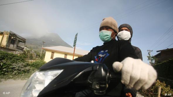 Villagers wear masks to protect themselves from the volcanic ash