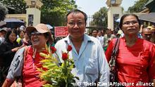 Zwei rot gekleidete Frauen und ein Mann mit roten Rosen in der Hand laufen über einen Platz