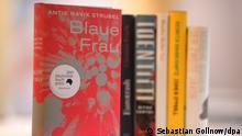 18.10.2021, Hessen, Frankfurt/M.: Das Buch Blaue Frau von Antje Ravik Strubel, für das Strubel mit dem Deutschen Buchpreis ausgezeichnet wurde, steht vor den Werken der anderen Autoren, die auf der Shortlist standen. Mit dem Deutschen Buchpreis wird der beste deutschsprachige Roman ausgezeichnet. Der Preis ist mit insgesamt 37 500 Euro dotiert. Der Preisträger erhält 25 000 Euro, die übrigen fünf Autoren der Shortlist erhalten jeweils 2500 Euro. Foto: Sebastian Gollnow/dpa POOL/dpa +++ dpa-Bildfunk +++