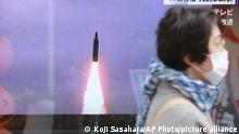 A woman walks past a TV screen showing North Korea fired missiles in a news program in Tokyo, Tuesday, Oct. 19, 2021. North Korea fired a ballistic missile into the sea on Tuesday in a continuation of its recent weapons tests, the South Korean and Japanese militaries said, hours after the U.S. reaffirmed its offer to resume diplomacy on the North's nuclear weapons program.(AP Photo/Koji Sasahara)
