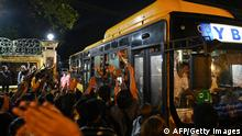 Newly-released prisoners wave from a bus as they depart the Insein Prison in Yangon on October 18, 2021, after authorities announced more than 5,000 people jailed for protesting against a February coup which ousted the civilian government would be released. (Photo by STR / AFP) (Photo by STR/AFP via Getty Images)