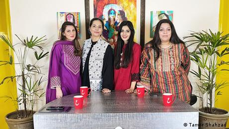 Four Pakistani femininst Youtubers stand at a grey table, with four mugs for coffee or tea