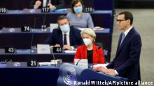 Poland's Prime Minister Mateusz Morawiecki, right, delivers his speech Tuesday, Oct. 19, 2021 at the European Parliament while European Commission president Ursula von der Leyen , in red, listens, in Strasbourg, eastern France. The European Union's top official locked horns Tuesday with Poland's prime minister, arguing that a recent ruling from the country's constitutional court challenging the supremacy of EU laws is a threat to the bloc's foundations and won't be left unanswered. (Ronald Wittek, Pool Photo via AP)