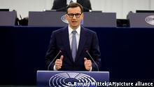 Poland's Prime Minister Mateusz Morawiecki, center, delivers his speech Tuesday, Oct. 19, 2021 at the European Parliament in Strasbourg, eastern France. The European Union's top official locked horns Tuesday with Poland's prime minister, arguing that a recent ruling from the country's constitutional court challenging the supremacy of EU laws is a threat to the bloc's foundations and won't be left unanswered. (Ronald Wittek, Pool Photo via AP)