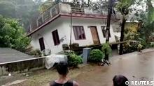 People watch a house being washed away in river due to strong current after heavy rains at Kottayam in Kerala, India, October 17, 2021 in this still image taken from video on October 18, 2021. REUTERS TV/ANI/KERALA GOVERNMENT PUBLIC RELATIONS OFFICE/ HANDOUT via REUTERS THIS IMAGE HAS BEEN SUPPLIED BY A THIRD PARTY. NO RESALES. NO ARCHIVES. MANDATORY CREDIT. INDIA OUT. NO COMMERCIAL OR EDITORIAL SALES IN INDIA.