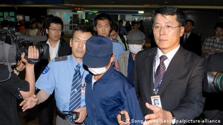North Korean defectors wear masks as they're escorted by South Korean government officials upon their arrival from Japan