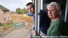 Maria Dunkel and Thomas Dunkel look out from their home's windows