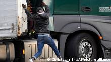 A migrant jumps on a truck to try to cross the tunnel heading to the UK, in Calais, northern France, Thursday, Oct. 14, 2021. In a dangerous and potentially deadly practice, he is trying to get through the heavily policed tunnel linking the two countries by hiding on a truck. (AP Photo/Christophe Ena)