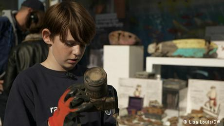 11-year-old Raphael, who is cleaning the Seine of scrap metal, holds a camera covered in mud