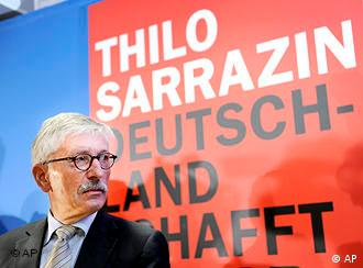 Thilo Sarrazin stands in front of a poster for his book