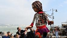 TOPSHOT - English actor Jude Law holds the hand of 'Little Amal', a giant puppet depicting a Syrian refugee girl, as she walks along the sea front at the harbour in Folkestone, south east England, on October 19, 2021 after arriving from Calais, as part of the international art project The Walk. - 'Little Amal' was designed by The Handspring Puppet Company and represents a Syrian refugee child and the millions of displaced children worldwide. 'Little Amal' is making a 8000 km journey across Europe to the United Kingdom to raise awareness of the challenges faced by refugee children. (Photo by Glyn KIRK / AFP)
