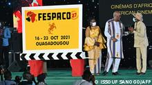 President Roch Marc Christian Kabore of Burkina Faso (2ndR) chats with Senegalese Minister of Culture Abdoulaye Diop (R) and Burkina Faso Ministre of Culture, Arts and Turism Elise Ilboudo Thiombiano (C) during the 27th Pan-African Film and Television Festival (FESPACO) opening ceremony on October 16, 2021 at the palais des sports in Ouagadougou (Photo by Issouf SANOGO / AFP)