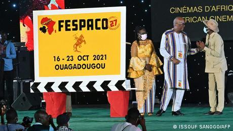 Eröffnungsveranstaltung des Filmfestivals FESPACO. Eine riesige Filmklappe ziert des Logo des Festivals. Daneben stehen der Leiter des Festivals sowie weitere Organisatoren.