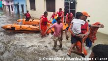 Members of National Disaster Response Force (NDRF) evacuate people to safer places from a flooded area in Udham Singh Nagar in the northern state of Uttarakhand, India, October 19, 2021. National Disaster Response Force/Handout via REUTERS ATTENTION EDITORS - THIS IMAGE WAS PROVIDED BY A THIRD PARTY. NO RESALES. NO ARCHIVES.