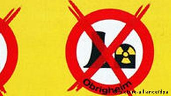 A passer-by looks at a placard campaigning against nuclear power