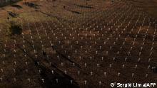Centenas de cruzes brancas espalhadas no gramado em frente ao Congresso Nacional, em Brasília. Taxa de mortalidade por grupo de 100 mil habitantes no Brasil subiu para 287,7