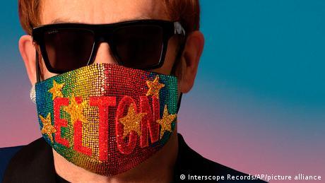 Elton John wearing sunglasses and a mask.