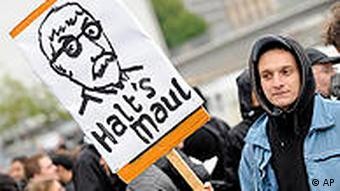 A protester holds a banner telling Sarrazin to 'shut up'