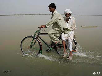 Mit dem Fahrrad durch das Wasser: Pakistanische Flüchtlinge in Punjab (Foto: AP)