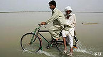 Crossing a flooded road in Punjab province on Monday