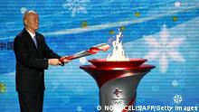 TOPSHOT - Communist Party Secretary of Beijing, Cai Qi, lights the cauldron during the Olympic flame welcoming ceremony ahead of the Beijing 2022 Winter Olympics, in the lobby of the Olympic Tower in Beijing on October 20, 2021. (Photo by Noel Celis / AFP) (Photo by NOEL CELIS/AFP via Getty Images)