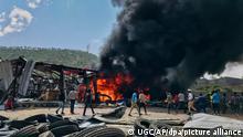 20.10.2021, Äthiopien, Mekelle: Menschen rennen nach einem Luftangriff auf die Hauptstadt der Region Tigray im Norden Äthiopiens vor schwarzen Rauchschwaden und Flammen. Die äthiopische Armee hat am Mittwoch (20.10.2021) einen weiteren Luftangriff auf die Hauptstadt der Krisenregion Tigray geflogen. Damit wurde die Stadt Mekelle zum zweiten Mal binnen drei Tagen bombardiert. Foto: ---/UGC/AP/dpa +++ dpa-Bildfunk +++