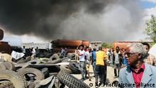 People are seen in front of clouds of black smoke from fires in the aftermath at the scene of an airstrike in Mekele, the capital of the Tigray region of northern Ethiopia Wednesday, Oct. 20, 2021. New airstrikes have hit Mekele, residents said Wednesday, as Ethiopia's government said it was targeting facilities to make and repair weapons, which a spokesman for the rival Tigray forces denied. (AP Photo)