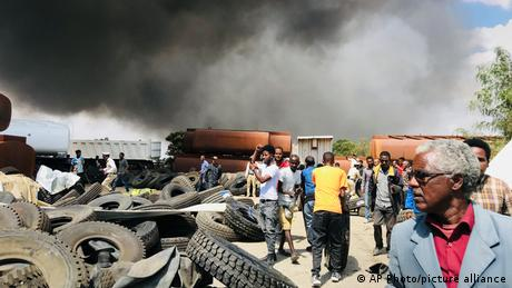 People are seen in front of clouds of black smoke from fires in the aftermath at the scene of an airstrike in Mekele