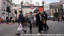 People wear face masks as they exit Piccadilly Circus underground station, in London, Tuesday, Oct. 19, 2021. Many scientists are pressing the British government to re-impose social restrictions and speed up booster vaccinations as coronavirus infection rates, already Europe's highest, rise once more. The U.K. recorded 49,156 new COVID-19 cases on Monday, Oct. 18, the largest number since mid-July. New infections averaged 43,000 a day over the past week, a 15% increase on the week before.(AP Photo/Alberto Pezzali)