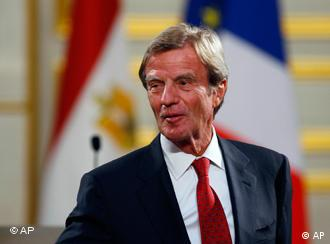 Bernard Kouchner in front of a French flag