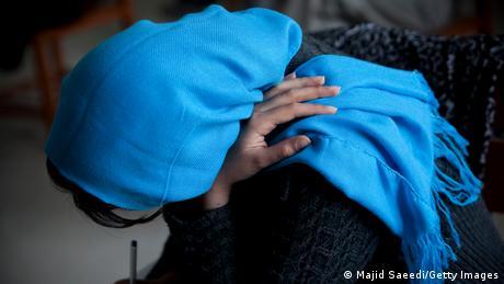 A female student wearing a headscarf, face hidden