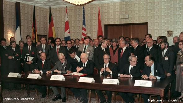 Foreign ministers at a table signing the agreement