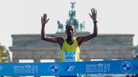 Ethiopia's Guye Adola celebrates as he crosses the finish line to win the Berlin Marathon in Berlin, Germany