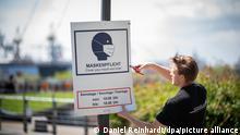 21.05.2021 Ein Mitarbeiter der Firma Scharlau hängt im Park Fiction ein Hinweisschild zur Maskenpflicht ab. Laut den vom Senat beschlossenen Lockerungen der Corona-Einschränkungen, fällt die abstandsunabhängige Maskenpflicht in den Grünanlagen entlang von Alster und Elbe ab dem 22.05.2021 weg.