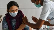 A woman gets a shot of a COVID-19 vaccine in Bangalore, India