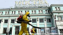 TOPSHOT - Servicemen of Russia's Emergencies Ministry wearing protective gear disinfect Moscow's Belorussky railway station on October 20, 2021, amid the ongoing coronavirus disease pandemic. - Russia said Wednesday 1,028 people died of Covid over the past 24 hours, a new record, as President Vladimir Putin mulls introducing nationwide restrictions to curb the spread of the disease. (Photo by Kirill KUDRYAVTSEV / AFP) (Photo by KIRILL KUDRYAVTSEV/AFP via Getty Images)