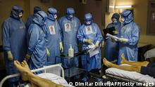 TOPSHOT - Medics wearing personal protective equipment (PPE) work in the intensive care unit for Covid-19 coronavirus patients in the Moscow Sklifosovsky emergency hospital in Moscow on October 20, 2021. - Russia said on October 20, 1,028 people died of Covid over the past 24 hours, a new record, as President Vladimir Putin mulls introducing nationwide restrictions to curb the spread of the disease. (Photo by Dimitar DILKOFF / AFP) (Photo by DIMITAR DILKOFF/AFP via Getty Images)