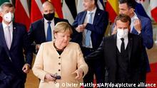 21.10.2021, Belgien, Brüssel: Bundeskanzlerin Angela Merkel (M) spricht mit Emmanuel Macron (vorne rechts), Präsident von Frankreich, während eines Gruppenfotos. Auf der Tagesordnung für den Gipfel der EU-Staats- und Regierungschefs stehen Diskussionen über die zuletzt stark gestiegenen Energiepreise in der EU, den digitalen Wandel und die Entwicklung der Corona-Pandemie. Zudem soll es u.a. eine Strategiedebatte über die Handelspolitik der EU und Gespräche über außenpolitische Themen geben. Foto: Olivier Matthys/AP/dpa +++ dpa-Bildfunk +++