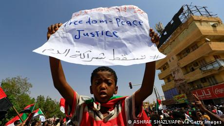 A young Sudanese demonstrator lifts a placard as protesters take to the streets of the capital Khartoum