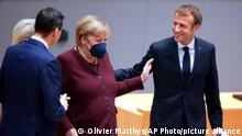 French President Emmanuel Macron, right, speaks with German Chancellor Angela Merkel, center right, as European Commission President Ursula von der Leyen, left, speaks with Poland's Prime Minister Mateusz Morawiecki during a round table meeting at an EU summit in Brussels, Friday, Oct. 22, 2021. European Union leaders conclude a two-day summit on Friday in which they discussed issues such as climate change, the energy crisis, COVID-19 developments and migration.(AP Photo/Olivier Matthys, Pool)