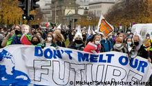 People walk past the Brandenburg Gate as they take part in a 'Fridays For Future' climate protest rally in Berlin, Germany, Friday, Oct. 22, 2021. (AP Photo/Michael Sohn)