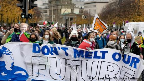 People walk past the Brandenburg Gate as they take part in a 'Fridays For Future' climate protest rally in Berlin