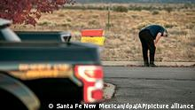 Alex Baldwin, de pé, com as mãos nos joelhos e cabeça baixa. Ao fundo, há uma paisagem de deserto, Na frente, desfocada, a traseira de uma caminhonete.