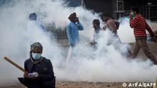 Activists from Tehreek-e-Labbaik Pakistan (TLP) take cover as police use tear gas to disperse the crowd as they march towards capital Islamabad from Lahore on October 23, 2021, demanding the release of their leader Hafiz Saad Hussain Rizvi, son of late Khadim Hussain Rizvi, founder of hardline religious political party Tehreek-e-Labbaik. (Photo by Arif ALI / AFP)