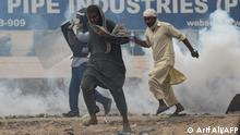 Tehreek-e-Labbaik Pakistan (TLP) supporters take cover as police use tear gas to disperse the crowd