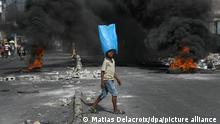 Ein Junge, der Wasser in Beuteln verkauft, läuft in der Nähe einer brennenden Barrikade an einer von Regierungsgegnern errichteten Straßensperre vorbei. +++ dpa-Bildfunk +++